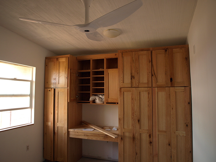 bedroom closet cabinets ceiling fan and light fixtures installed