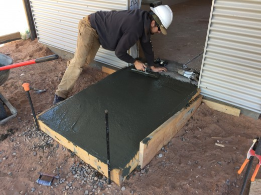 Josh finishing the concrete slab out front of the kitchen entrance.